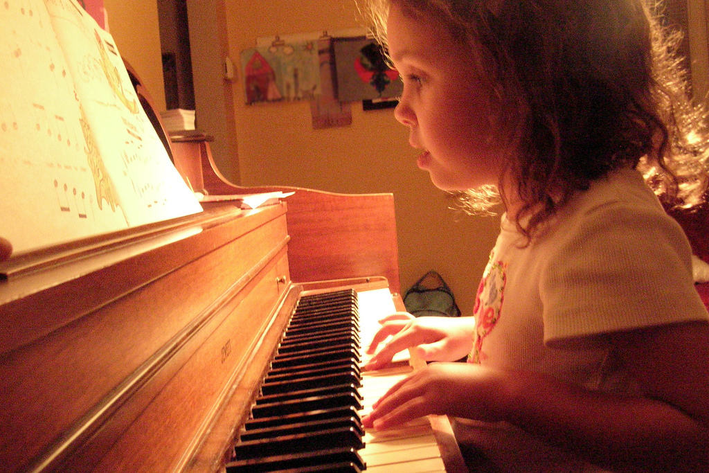a girl plays piano while reading notes
