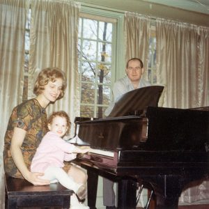 parents encouraging their child to play piano