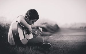 young man playing the guitar outdoors
