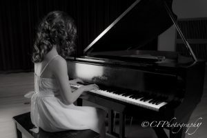 Girl sitting at the piano playing.