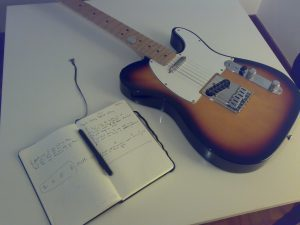 song composition book and guitar