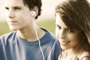 Teens sharing earphones, listening music outdoor. Summer time.