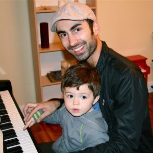 father and son playing the piano
