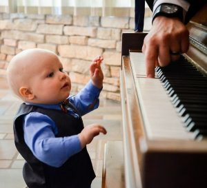 little boy trying to play the piano