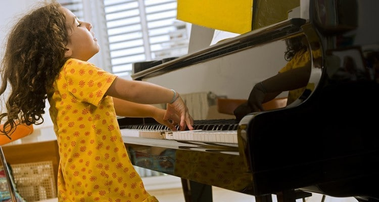 girl enjoys playing the piano