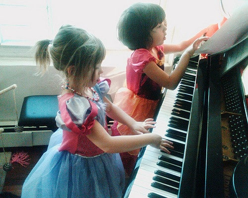 two children playing the piano