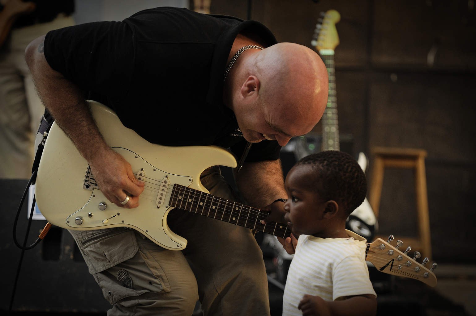 Tech. Sgt. Jason Cale, U.S. Air Forces in Europe and Air Forces Africa band guitarist, offers a child a chance to play his guitar during a concert in Dakar, Senegal, June 14, 2014, at a local cultural center. USAFE-AFAFRICA Airmen are in Senegal for African Partnership Flight, a program designed to improve communication and interoperability between regional partners in Africa. The band will be playing multiple venues in the area to inspire children and musicians through the universal language of music. (U.S. Air Force photo/ Staff Sgt. Ryan Crane)