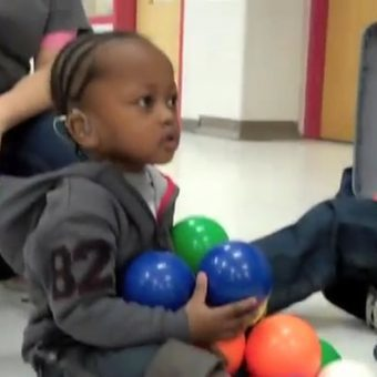 little girl playing with colored balls