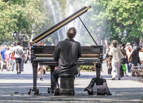 man playing the piano on the streets