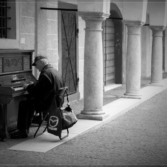 man playing piano on the streets
