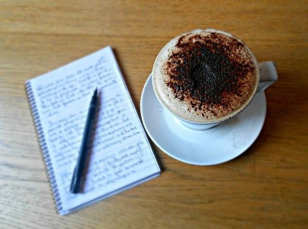 a songwriter's book and cup of coffee